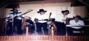 Old photograph of Jack Silva playing country music with bandmates on stage.