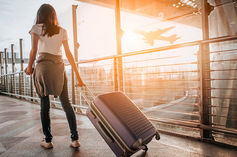 Travel plans and coronavirus - What should you do? A woman walks with her suitcase at an aiprort.