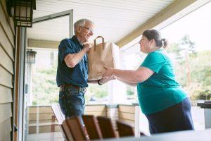 women hands older adult a bag of food.