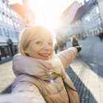 older adult takes a selfie while traveling, which isn't advised during the coronavirus outbreak.