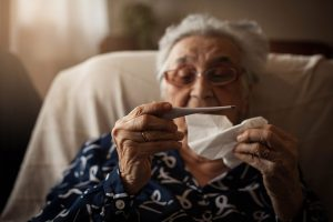 symptoms, like this older women holding a thermometer, is answered in this COVID-19 FAQ.