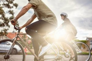 couple riding bike as getting exercise and being outdoors is on the list of ideas for social distancing.