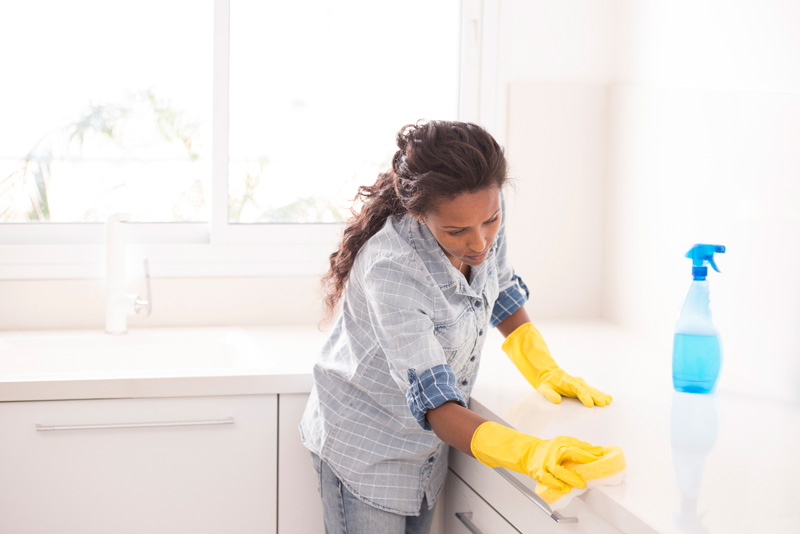 woman disinfecting coronavirus by wiping down countertops in the kitchen.