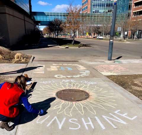 UCHealth volunteers chalk the walk outside of UCH.