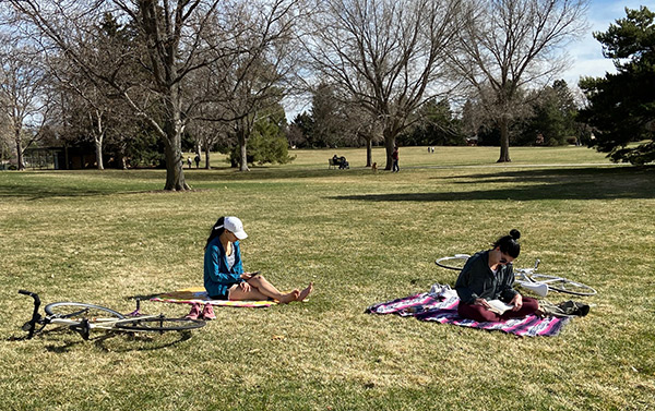 Women in Denver practice physical distancing. They are sitting about six feet apart in a park.