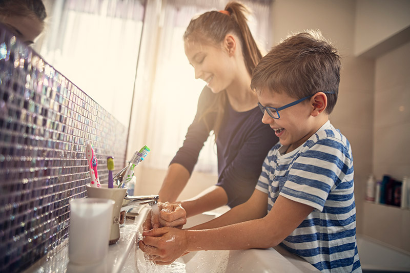 kids laughing while washing their hands, important in preventing the spread of coronavirus.