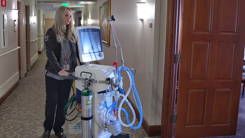 nurse wheels in a ventilator for treatment of COVID-19 patient with ARDS.