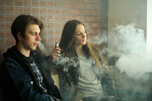 a young man and a woman vaping, and the coronavirus makes this more risky.