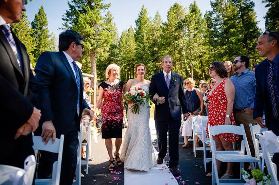 Dr. Michael Douglas and his wife, Meg, walk their daughter down the aisle at her wedding. Michael is the first patient in Colorado to have received convalescent plasma to help fight COVID-19.