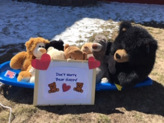 teddy bears in a front lawn with words of encouragement, one of the ways people are connecting during covid pandemic