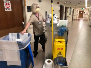 Margaret Waggett washes her hands outside a patient's room at UCHealth Memorial Hospital Central