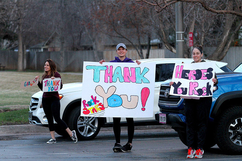 three young women hold signs, showing their thanks to health care workers in Colorado during Covid-19 outbreak