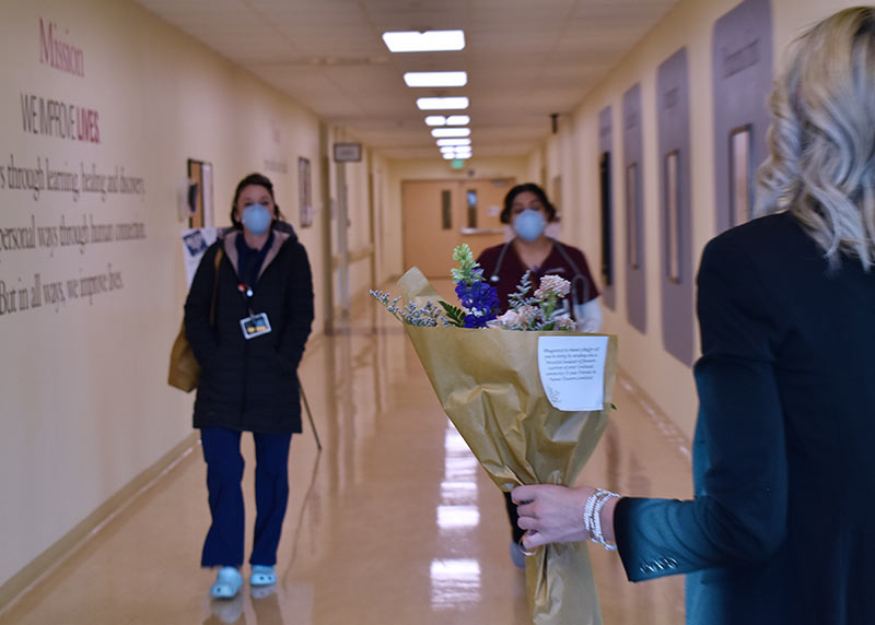 two health care workers walk down a hospital hallways towards a boutique of flowers donated as thanks.