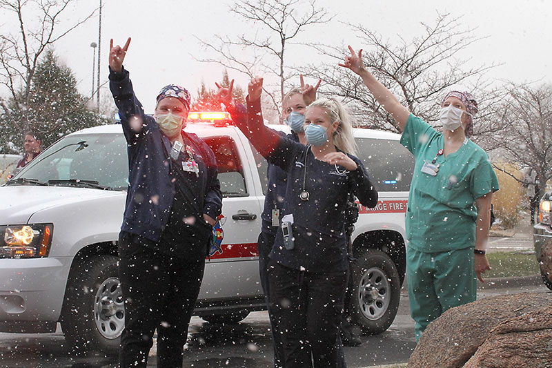 Health care workers at MCR wave to first responders parading through their hospital parking lot, one way Colorado thanks UCHealth health care workers.