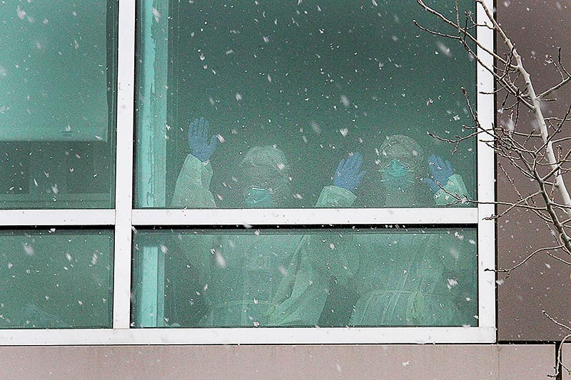 health care nurses in PPE wave thanks out the window of a hospital.