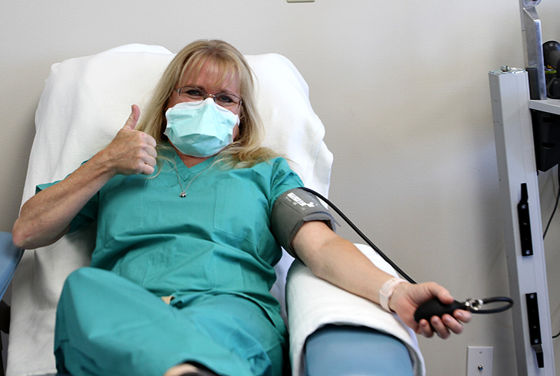 Julie gives a thumbs up as she sits in the plasma donation chair.
