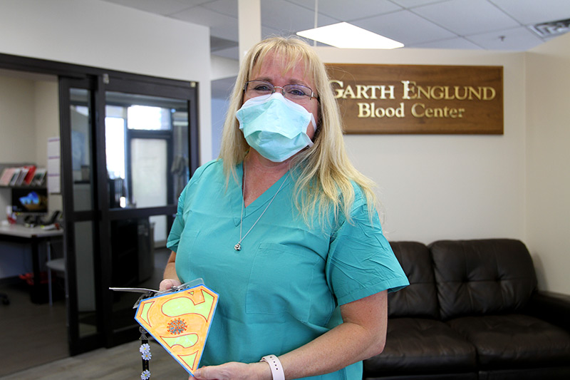 Julie Christen shows off her COVID superpower badge her friend made her as she stands in front of the Garth Englund Blood Center sign.