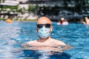 is water and swimming safe during COVID pandemic? A man in mask and sunglasses at a swimming pool.