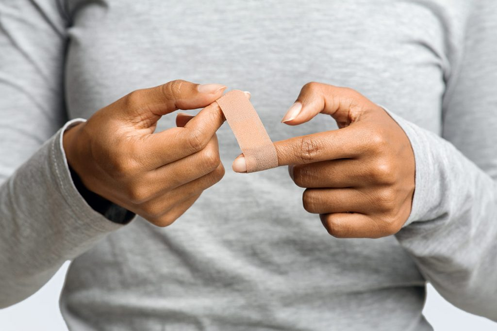 a woman wraps a Band-Aid around her finger to start the wound healing process.