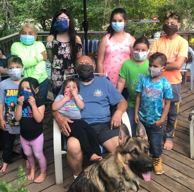 Sam with grand kids on porch all wearing masks