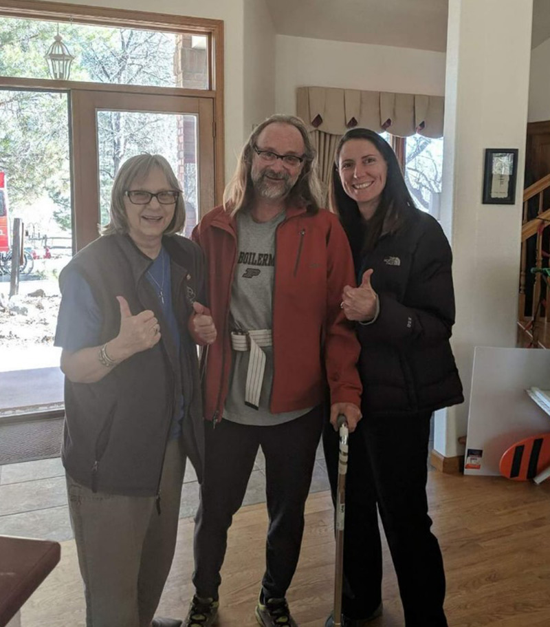 three people stand with their thumbs up inside Jeff's home as a sign that his home is safe to return to after Jeff's hemorrhagic stroke treatment