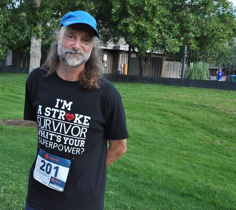 Jeff with a t-shirt that says I'm a stroke survivor, what's your superpower. Jeff received hemorrhagic stroke treatment at UCHealth Medical Center of the Rockies.