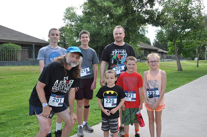 Jeff with his grandkids, all wearing race numbers.