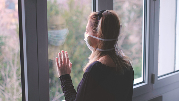 woman looking worried out her window in a mask - behavioral health in primary care