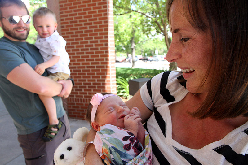 mom holds newborn with son and father in the background. Mom and daughter are part of four generations born at the same hospital.