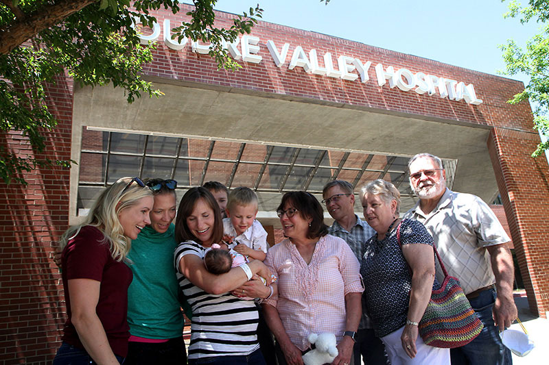 family members stand outside poudre valley hospital, including the 4 generations born at that same hospital..