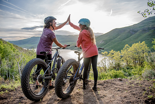 Camping in Colorado during COVID-19 can help you enjoy the outdoors. Here, two women high five during a bike ride in a state park.