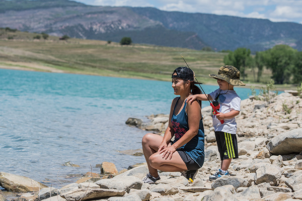 Camping in Colorado durnig COVID-19 can be a great escape. Here, a mother and her son fish at Harvey Gap State Park.