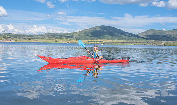 Camping in Colorado durnig COVID-19 can be a great escape. Here, a man kayaks at Vega State Park.