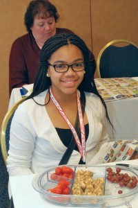 Keylani Warfield poses with healthy snacks in a workshop taught by Kathleen Splane, FCS agent