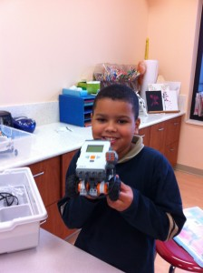 A young boy holds up a robot