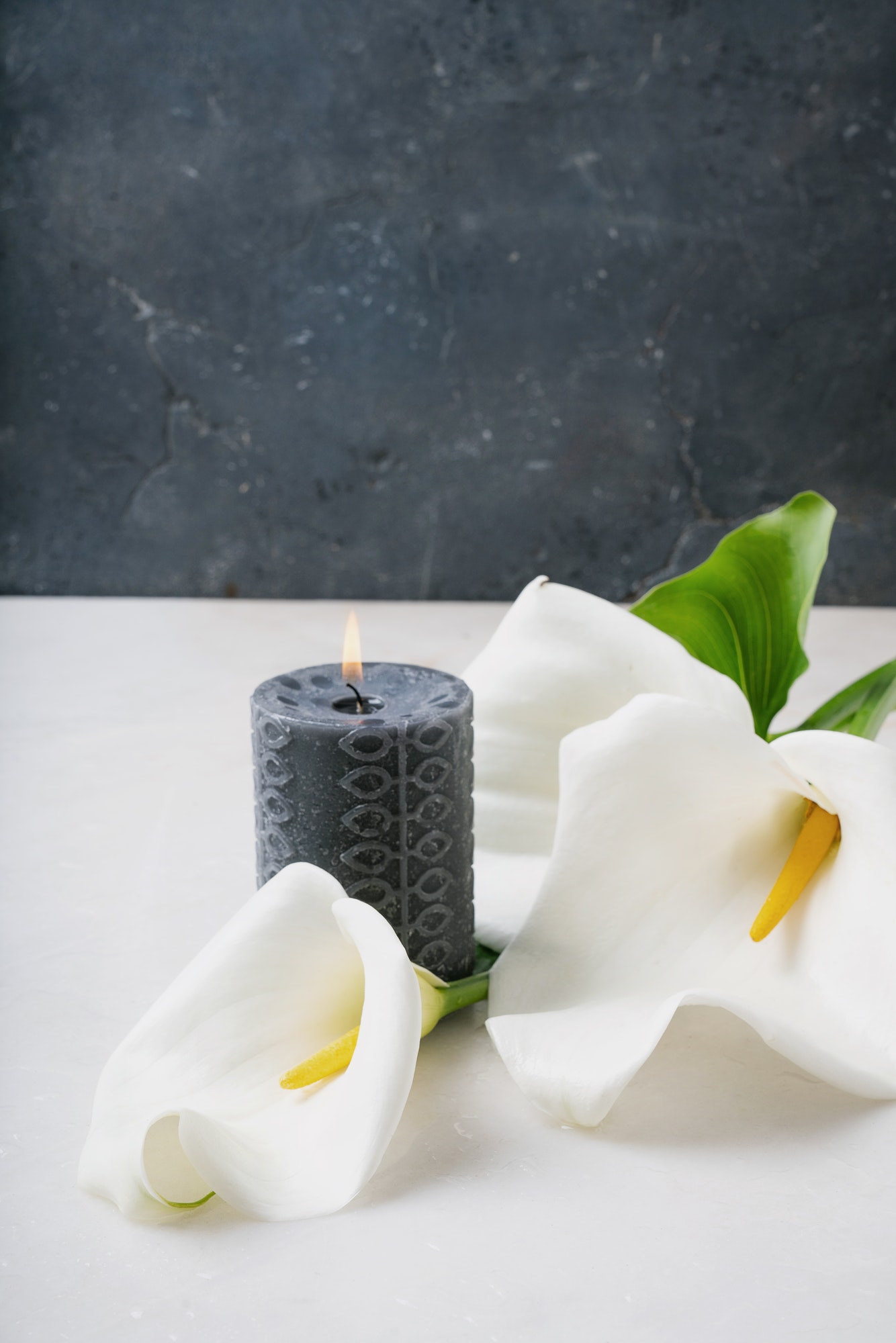 White Calla Lilly flowers with burning black candle