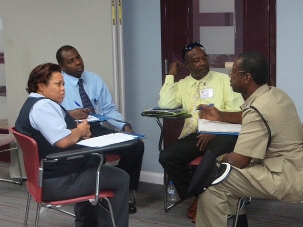 Participants from diverse agencies discussing how to respond to one of the IMO scenarios