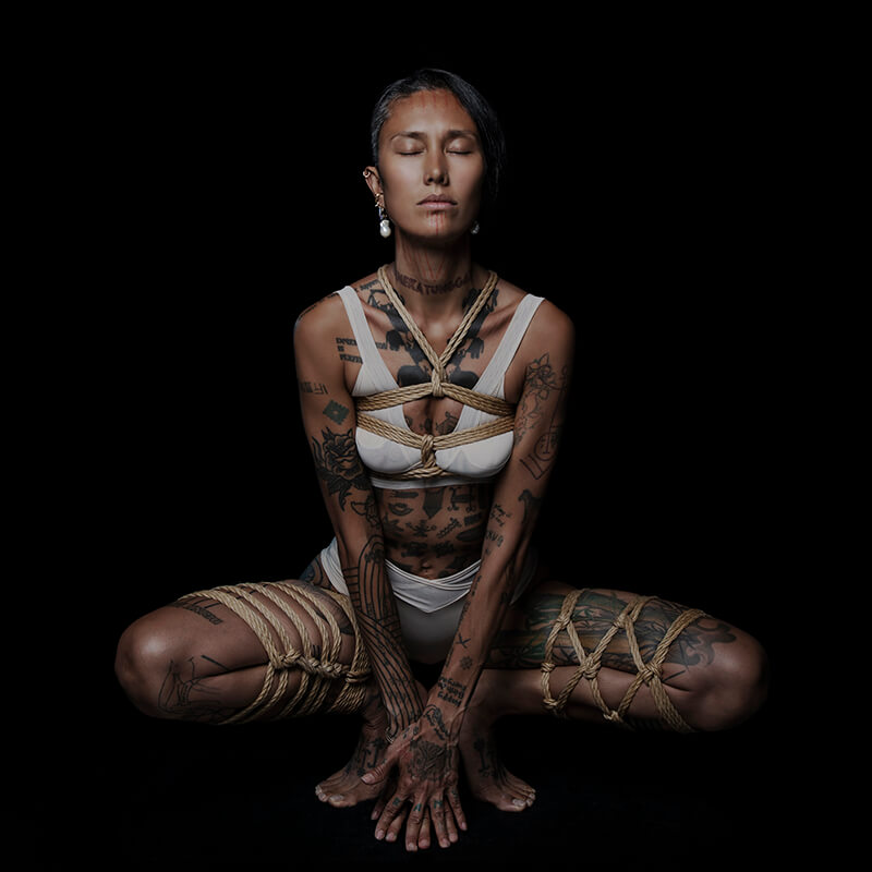 Tattooed Shibari model sitting tied with rope harness