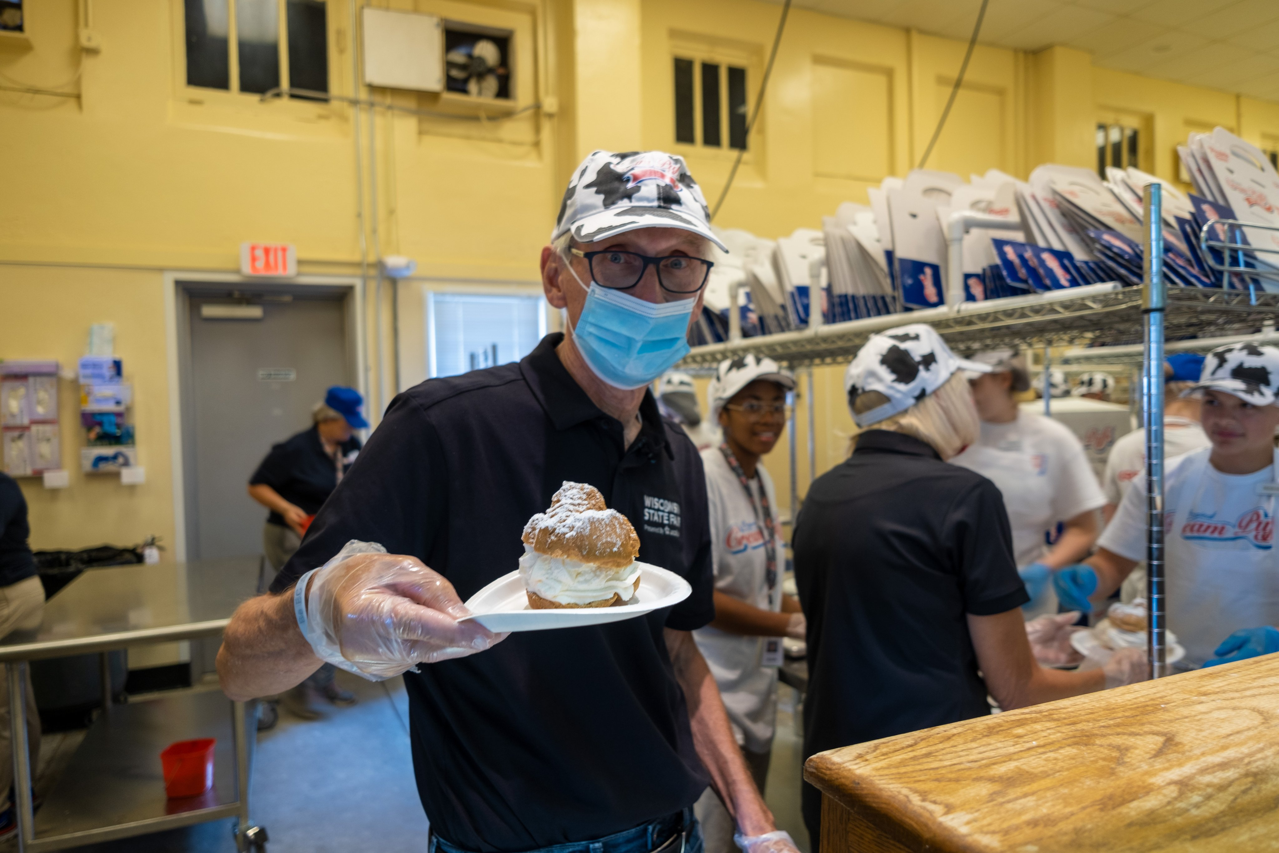 Gov. Evers serves up a cream puff at the Wisconsin State Fair. More than 250 fairgoers have earned a free cream puff by getting vaccinated at the fair's vaccine clinic.