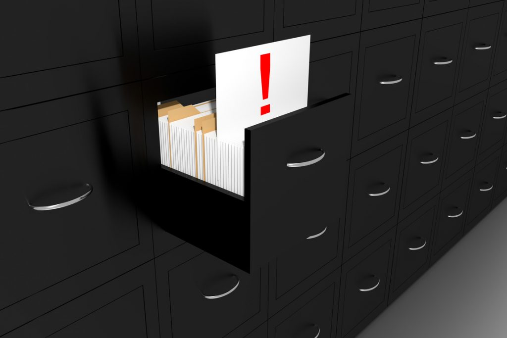 open file cabinet drawer with an open file marked with an exclamation point