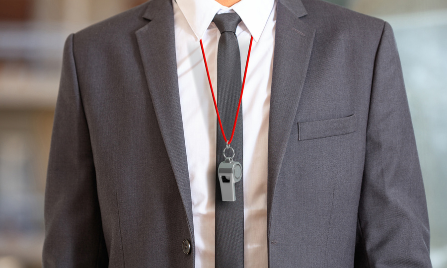 Person in suit with a whistle on a cord around neck