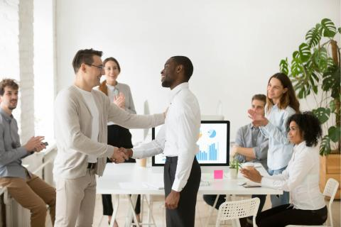 group of office workers welcoming a man with handshakes