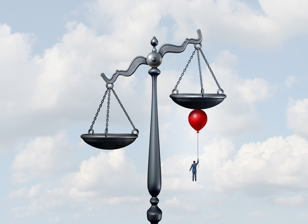 Scales of justice with a businessperson holding a balloon rising under one side of the scales