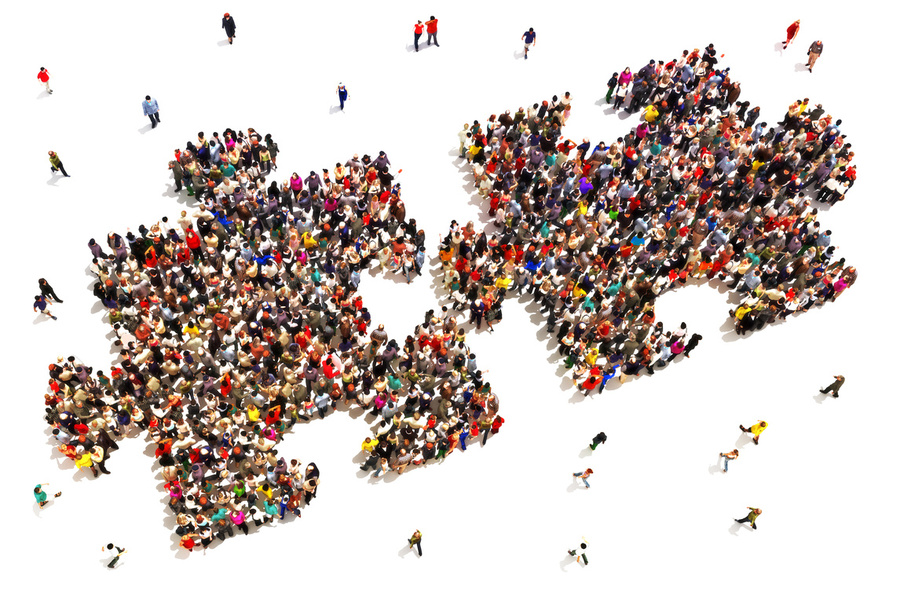 Overhead image of lots of people, standing in the shape of two puzzle pieces