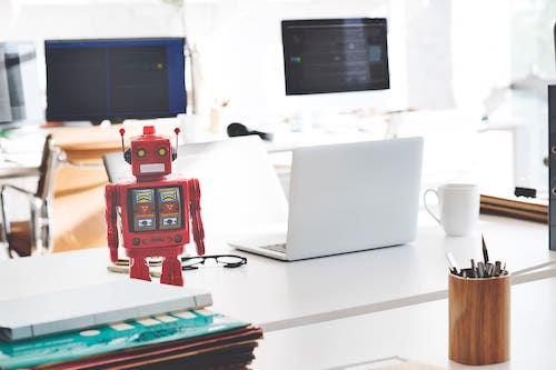 Mini robot on a desk with a computer