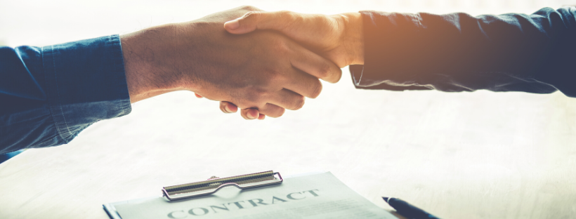 A handshake over a paper contract.