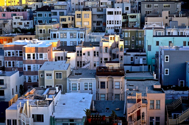 A low aerial view of a city neighborhood with a variety of types of buildings, including apartments, town homes, and brownstones illustrating the variety of homes available to real estate buyers.