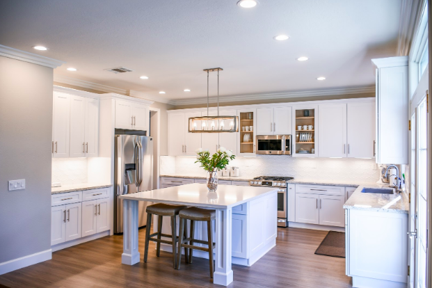 An upgraded kitchen with stainless steel appliances, a large island with a breakfast bar and kitchen stools, high ceilings and recessed lighting.