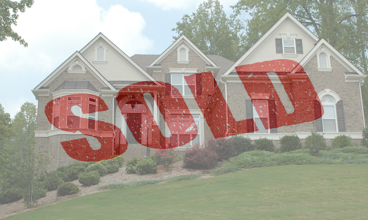 Beautiful home with landscaped lawn, with the word Sold superimposed in bold red font.