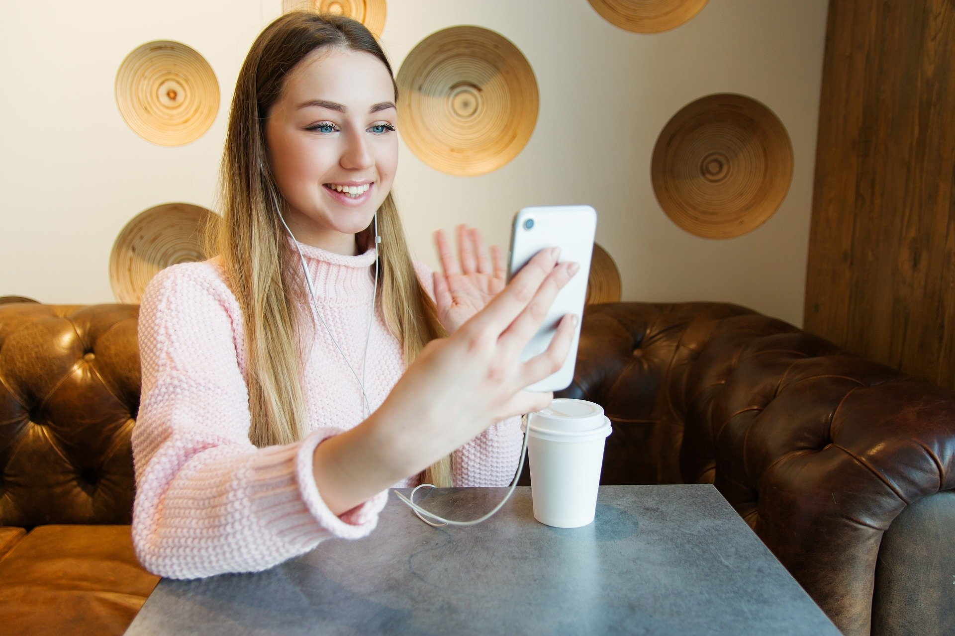 A girl wearing headphones holds up a phone and waves to someone on e video call. She sits on a brown couch and a grey table and a white travel coffee cup sits on the table.